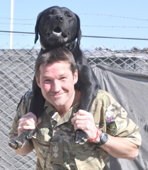 "Lt Col Eastman demonstrates the ""carry"". The dogs find difficulty climbing compound walls and so are carried over by their handlers in this manner."