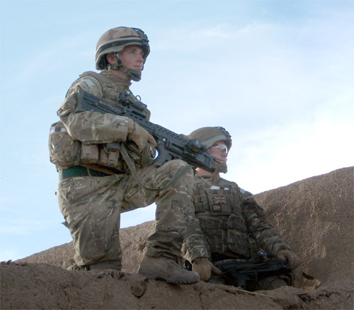 Lance Corporal Roberts and one of his men look out over the Green Zone from the roof of a compound.