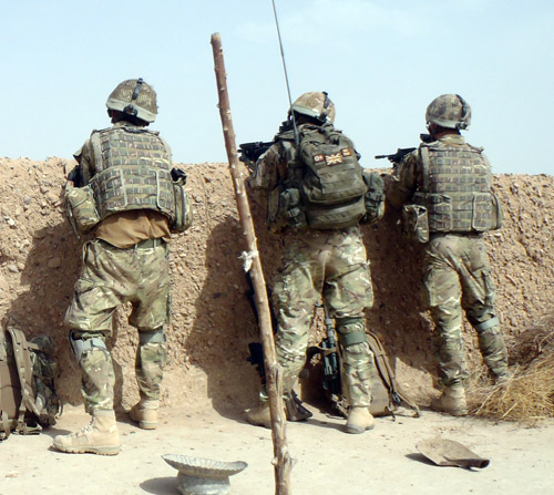 Lance Corporal Roberts and his fire team take up a fire position over the wall of a compound.