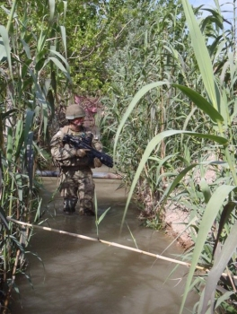 Corporal Taylor patrols through an irrigation ditch in the Green Zone.