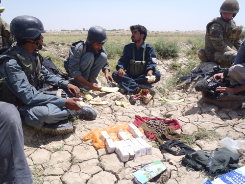 What the ANP officer found hidden in the field - right next to the melon he's eating - 1,000 rounds of the insurgent's 7.62mm ammunition.