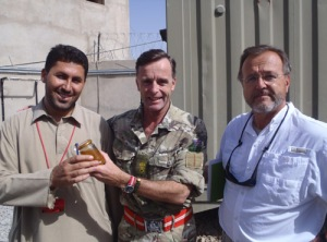 John presenting Lt Col Tim Purbrick with a pot of Helmand honey with Don Welty on the right