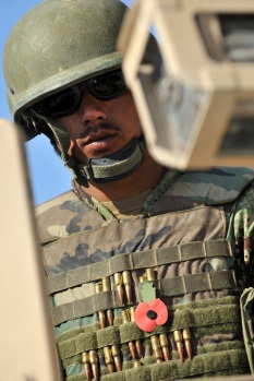 An Afghan Soldier wears his poppy amongst his ammunition