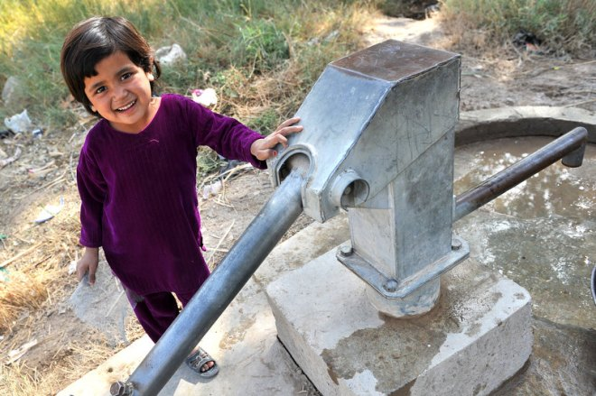 A little girl laughs at us as we approach the well