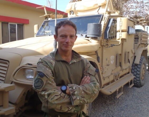 Lieutenant Matt Galante at Paind Kalay police station with Husky vehicle in background. Crown Copyright/MOD 2011