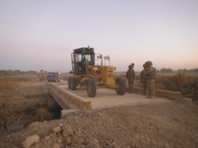 A tractor drives over the finished bridge.