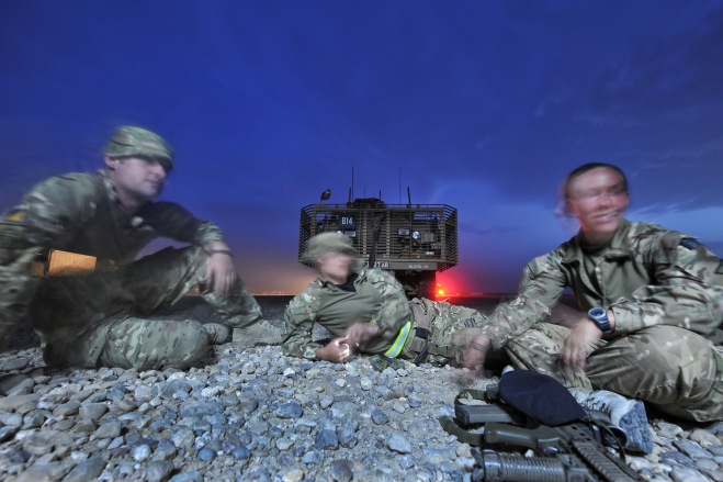 Three soldiers relax at dusk during a break in a Combat Logistic Patrol
