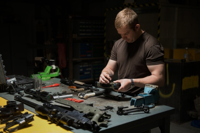 An armourer working on a rifle.