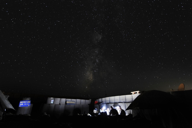 Soldiers in FOB Ouellette play cards by torchlight under the night sky
