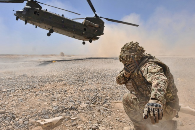A Landing Point Commander shields himself from the downwash of a Chinook