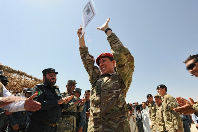 A Royal Military Policewoman receives an award from the ANSF and celebrates in the usual Afghan manner