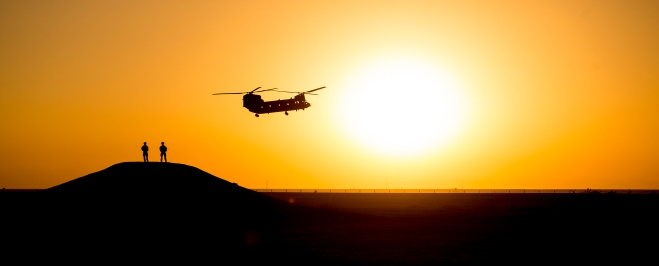A Chinook departs Camp Bastion under a setting sun