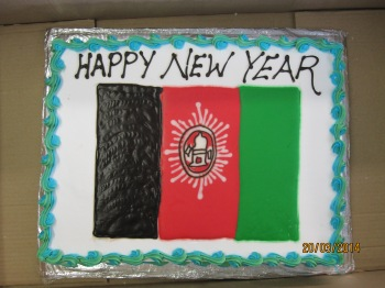 A cake decorated with the Afghan flag and the words 'Happy New Year'.