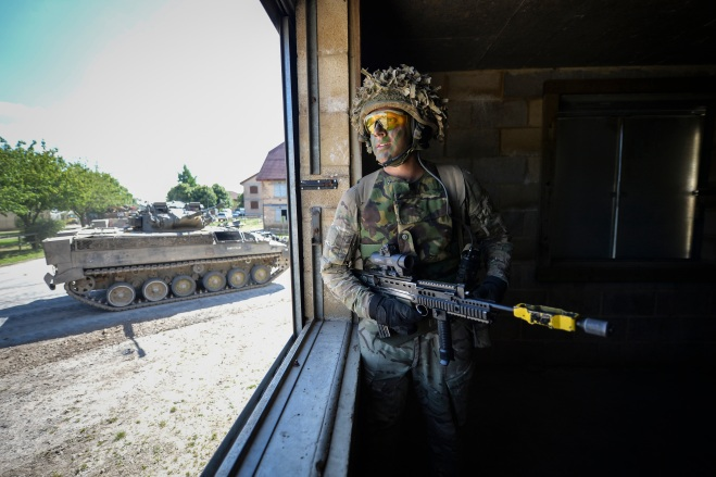 A section commander keeps watch over his men during a battle through an urban area.