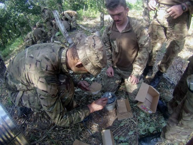 Spr Magee helping Royal Marines to make improvised claymore mines